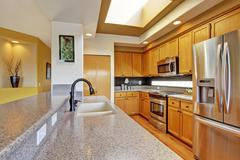 Kitchen room with steel appliances and granite tops Stock Photos