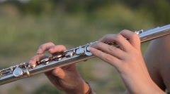 Female plays flute outdoors Stock Footage