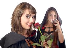 two young women in disguise halloween with a glass of blood and a rose - stock photo