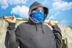 Man with a baseball bat on old wall background Stock Photos