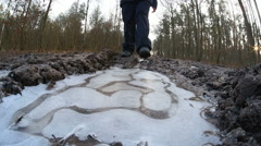 Walking and breaking the ice on the forest dirt road near Lublin, Poland Stock Footage