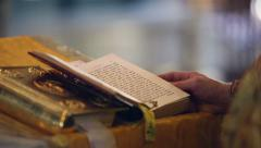 Reading the Holy Gospel. Hands Orthodox priest turns the page Stock Footage