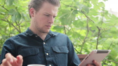Man reading on his tablet in front of fig tree drinking tea Stock Footage