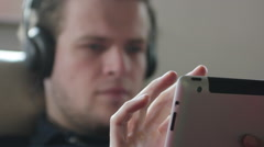 Man using his tablet to search for music - stock footage