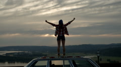 Young Woman Stands On Her Car, She Raises Her Arms And Jumps Up And Down Stock Footage