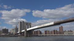 Pan left Brooklyn Bridge Pier 17 New York City panorama sunny day Freedom Tower  Stock Footage