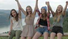4 Girls Sit On A Fence At A Viewpoint, They Hold Hands And Raise Them In The Air Stock Footage