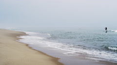 Cape cod surfer and beach overcast Stock Footage
