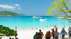Similans, thailand - circa mar 2014: tourists on the beach hiding in the shad Stock Footage