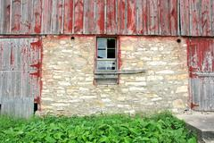 Old abandoned barn with broken window and two wood doors Stock Photos