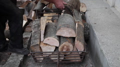Man, worker loading cart with firewood, wood logs, stumps, winter supplies Stock Footage