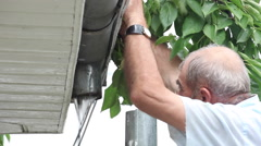 Man cleaning clogged gutter,connecting,fixing, downspout,drainpipe,flowing water Stock Footage