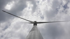 Big blades of a  wind energy generator turn under white clouds Stock Footage