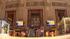 Railway station indicator board,passengers,travellers, commuters, escalators Stock Footage