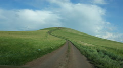 Vehicle Shot of a car climbing a green hill on the grasslands Stock Footage
