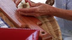 A lady peeling and preparing fresh garlic to make italian bruschetta Stock Footage