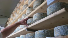 0432 UHD Worker in a cheese factory working on cheeses aging Stock Footage