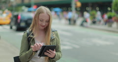 Young Caucasian blond woman using tablet pc in city - stock footage