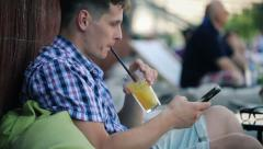 Trendy man texting on smartphone drinking juice in outdoor cafe HD Stock Footage