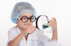 Chemist enthusiasm considering flask under a magnifying glass Stock Photos