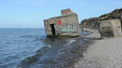Bomb shelter with graffiti on shore of baltic sea - stock footage