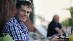 Young happy man with tablet computer sitting in outdoor bar HD Stock Footage