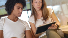 couple of attractive young people use tablet computer and communicate - stock footage