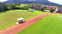 Kids on bicycle speeding down the track aerial shot Stock Footage