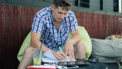 Young student doing homework with tablet computer help in cafe HD Stock Footage