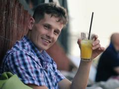 Young man raising toast to camera in outdoor bar NTSC Stock Footage