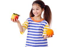smiling girl with apple and orange - stock photo