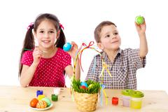 Two kids paint easter eggs Stock Photos
