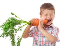 Stock Photo of little boy biting the carrot