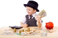 Stock Photo of boy at the table counts money