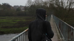 Hooded Teen Walking Along Bridge Stock Footage