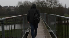 Hooded Man Walking Along a Bridge in Rain - stock footage