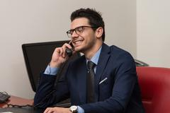 businessman talking on telephone and using computer - stock photo