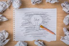 pencil erase and hand drawn light bulb on paper with crumpled paper - stock photo