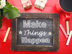 Make things happen on chalkboard on red table Stock Photos