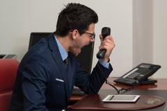angry man in formal wear shouting at phone - stock photo