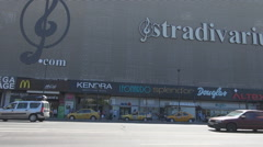 Advertise on mall building, cars driving in front of shopping store, summer day Stock Footage