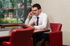 Businessman talking on telephone and using tablet Stock Photos
