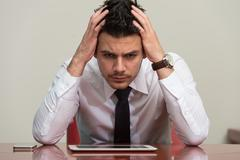 Stock Photo of overworked businessman sitting by his desk