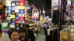 Pedestrians Pass T-shirt Shops at Night Stock Footage