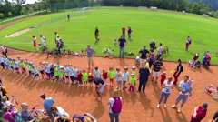 Kids standing in line and waving to flying camera Stock Footage