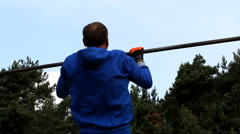 Man doing pull-ups outdoors Stock Footage