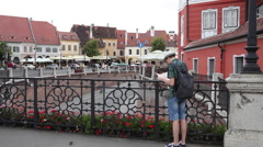 Beautiful medieval town, young man lost, tourist on a bridge, map, street,Europe Stock Footage