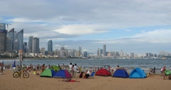 4k many people at crowded sandy beach.People swimming in sea,QingDao,China. Stock Footage