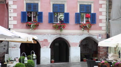 Beautiful pink house, blue wood shutters, blinds, flowers, old European town Stock Footage