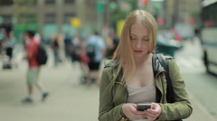 Young Caucasian blond woman texting cellphone in city - stock footage